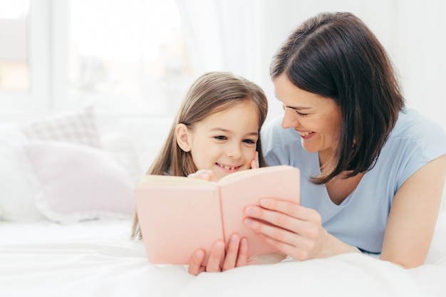 Pleasant looking female child with curious expression, reads interesting book together with her affectionate mother