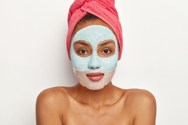 Pleasant looking female model with fresh skin, applies beauty mask, wears pink towel on head, stands with bare shoulders, looks directly
