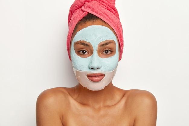 신선한 피부를 가진 유쾌한 여성 모델, 미용 마스크 적용, 머리에 분홍색 수건 착용, 맨손으로 어깨로 서서 직접보기
