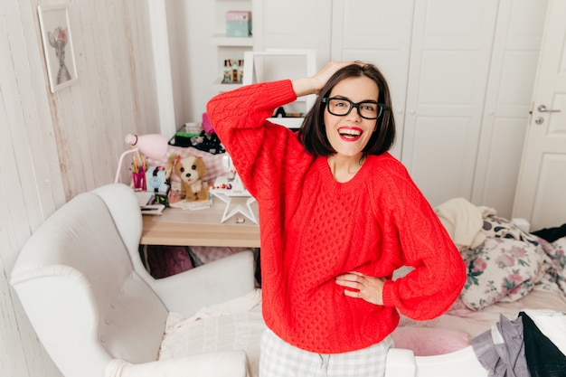 Pleasant looking female smiles joyfully, wears spectacles and red sweater