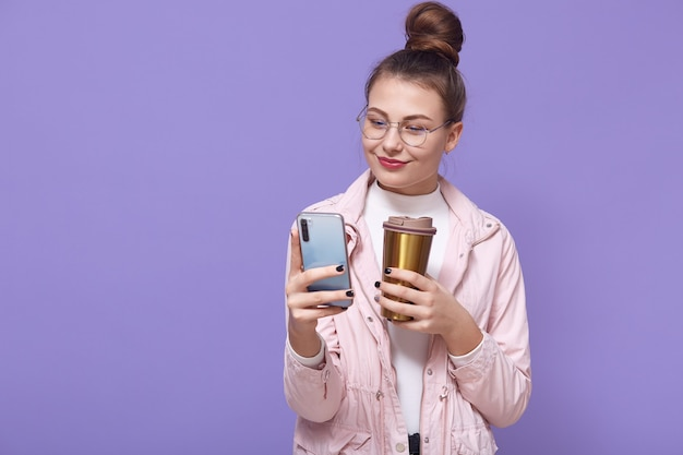 Pleasant looking female wearing spectacles and pale rose jacket posing isolated over lilac wall, drinking hot beverage from thermo mug, holding smart phone in hands and browsing internet.