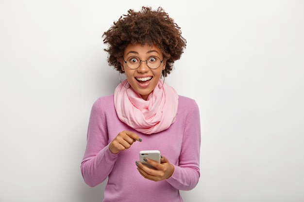 Pleasant looking female with crisp hair, points at cell phone device, donwloads new modern application, has happy expression, wears spectacles for vision correction, purple jumper and silk scarf