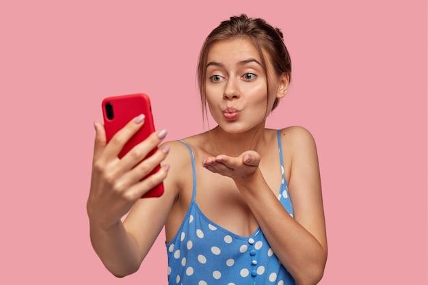 유쾌한 여자 친구가 스마트 폰으로 남자와 바람을 피우고, 화상 통화 중에 에어 키스를하고, 휴대 전화를 앞에두고, 캐주얼 한 여름 드레스를 입습니다.