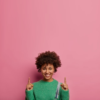 Pleasant looking glad woman invites going upstairs, points index fingers upwards, shows where to find best discounts, wears green sweater, models against rosy wall, advertises something