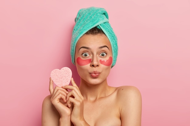 Pleasant looking green eyed european woman wears hydrogel patches under eyes for soothing delicate skin, reduces eye bags after tired work, has lips folded, holds cosmetic sponge for makeup.