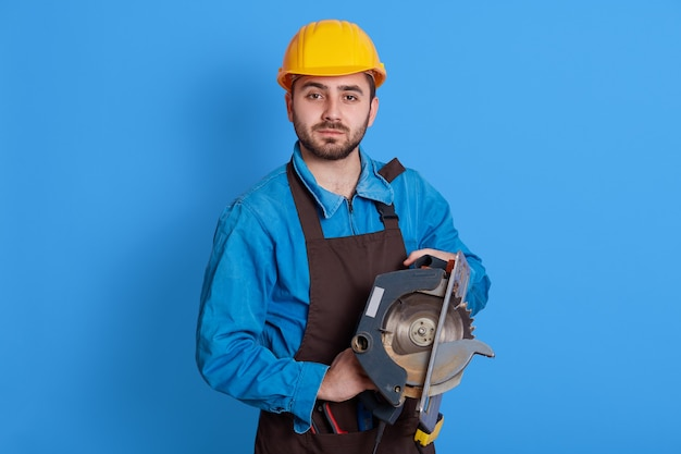 Pleasant looking handsome worker holding tool in both hands, looking  with serious expression, wearing brown apron, blue overall and yellow helmet, against color wall.