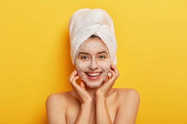 Pleasant looking happy woman unclogges pores, makes beauty step to improve skin, wears nourishing facial scrub, supples complexion, keeps hands on cheeks