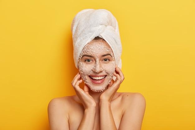 Una donna felice dall'aspetto piacevole sblocca i pori, fa un passo di bellezza per migliorare la pelle, indossa uno scrub viso nutriente, dona elasticità alla carnagione, tiene le mani sulle guance