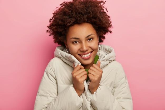 Piacevole donna felice con i capelli ricci, indossa un cappotto caldo e confortevole, ha una pelle sana e scura, sorride piacevolmente, isolato su sfondo roseo.