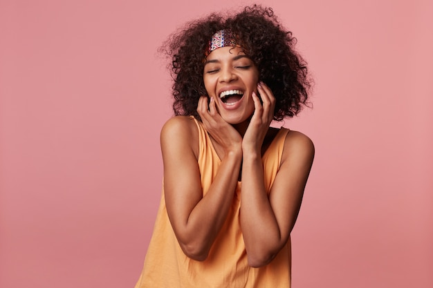 Giovane femmina bruna riccia dall'aspetto piacevole con la pelle scura che tiene le mani sulle guance e che sorride ampiamente con gli occhi chiusi, vestita con top arancione chiaro e fascia colorata