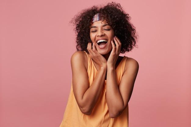 Приятно выглядящая счастливая молодая кудрявая брюнетка с темной кожей, держащая руки на щеках и широко улыбаясь с закрытыми глазами, одетая в светло-оранжевый топ и красочную повязку на голову