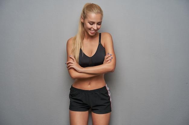 Piacevole cerca felice giovane donna sportiva con lunghi capelli biondi che indossa top nero e pantaloncini, in piedi su sfondo grigio chiaro con le mani giunte e sorridente positivamente
