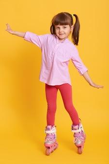 Pleasant looking kid raising hands while wearing roller skates