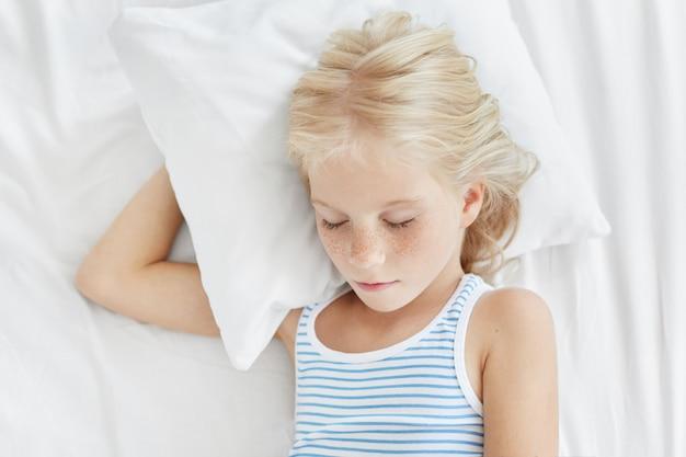 Piacevole bambina con i capelli biondi e la faccia lentigginosa, che dorme dolcemente sdraiata sul cuscino bianco chiudendo gli occhi, godendo di un'atmosfera calma e di condizioni confortevoli nella sua camera da letto