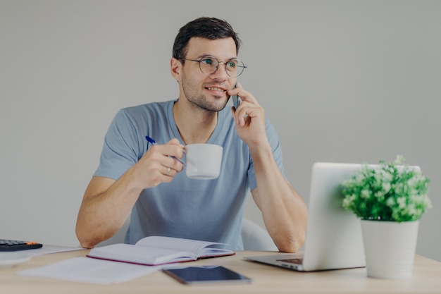 Pleasant looking male accountant in round glasses sips hot beverage, has mobile conversation