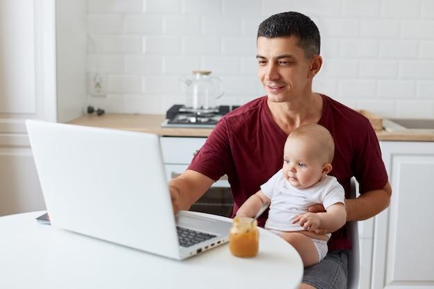 Приятно выглядящий мужчина в бордовой повседневной футболке, молодой взрослый отец сидит за столом на кухне перед портативным компьютером, глядя на дисплей ноутбука с позитивным выражением.