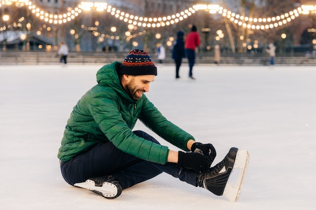Pleasant looking man wears green coat and hat, sits on ice and laces up skates, going to skate