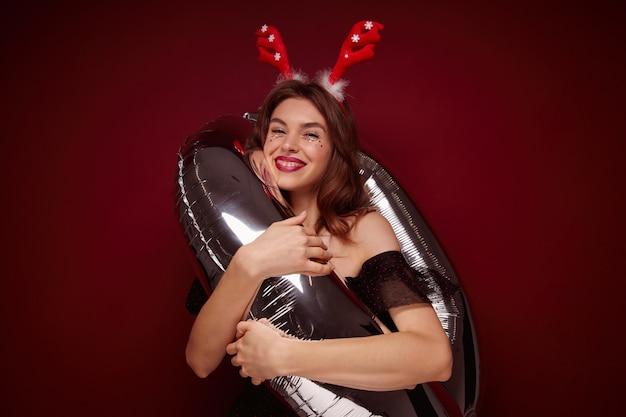 Piacevole giovane donna bruna dall'aspetto positivo vestita in abiti festivi e cerchio di vacanza abbracciando mongolfiera e sorridendo sinceramente, preparandosi per la festa di capodanno, isolato