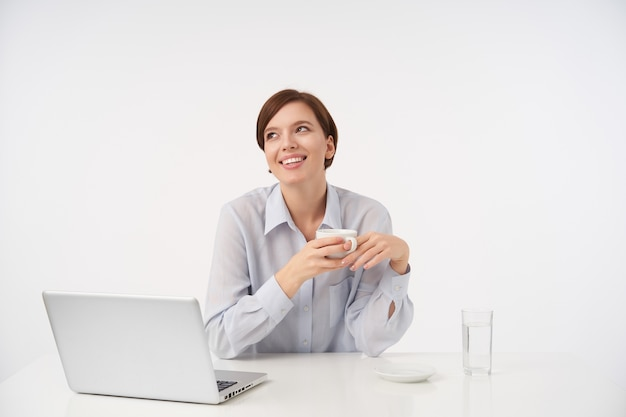 Приятно выглядящая позитивная молодая милая шатенка с короткой модной стрижкой пьет чашку чая, сидя на белом в строгой одежде