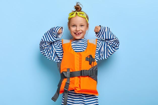 느슨한 줄무늬 선원 점퍼를 입은 유쾌한 redhaired 소녀, 팔을 들고, 힘을 보여주고, 바다에서 생명의 은인 척하고, 보호용 고글을 착용하고, 부풀린 구명 조끼가 힘을 보여줍니다.