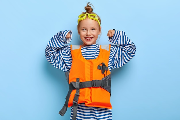 Pleasant looking redhaired girl in loose striped sailor jumper, raises arms, shows her strength, pretends being lifesaver at sea, wears protective goggles and inflated lifevest demonstrates power