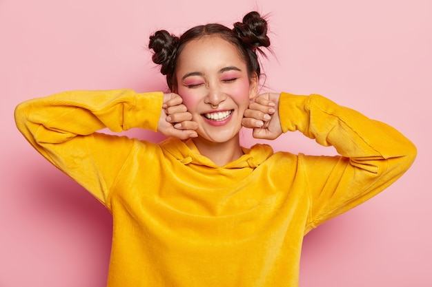 心地よい見た目の満足しているアジアの女性は、頬の近くに手を保ち、目を閉じ、黄色のベルベットのパーカーを着て、ピンクの化粧をして、前向きに笑います