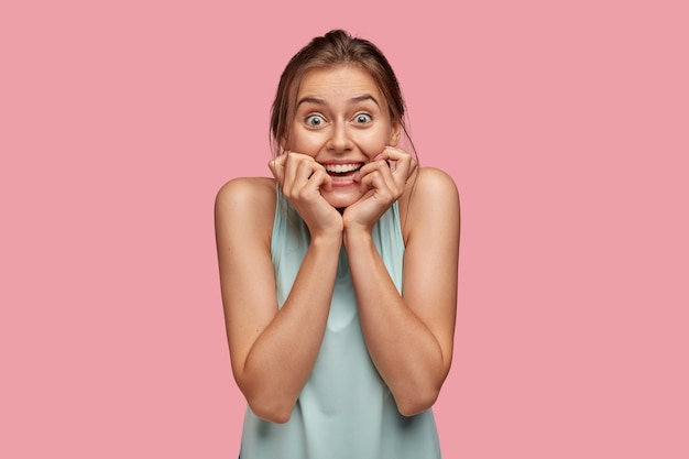 La giovane donna soddisfatta dall'aspetto piacevole sorride in generale tiene entrambe le mani vicino alla bocca, reagisce a qualcosa di positivo, modella contro il muro rosa. concetto di emozioni felici