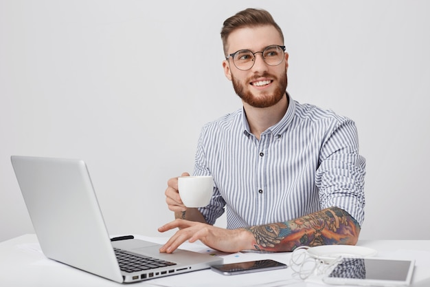 Pleasant looking stylish tattooed male enterpreneur or office worker