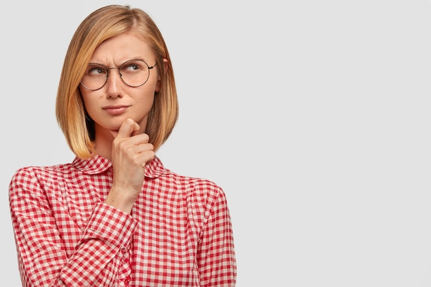Pleasant looking thoughtful woman tries to solve problem, keeps hand under chin