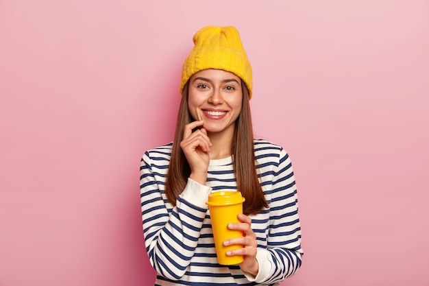 Pleasant looking woman adores coffee, holds takeaway cup, smiles pleasantly, wears yellow hat and striped sweater, poses over pink wall, enjoys smell