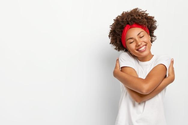 Una donna dall'aspetto piacevole si abbraccia, ricorda il momento romantico con il fidanzato, inclina la testa e chiude gli occhi con piacere