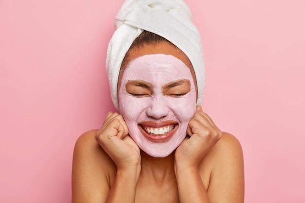 유쾌한 여자는 두 손을 뺨에 유지하고, 넓게 미소를 짓고, 하얀 치아를 보여주고, 머리에 감싸 인 수건을 착용하고, 분홍색 벽 위에 절연되어 있습니다.