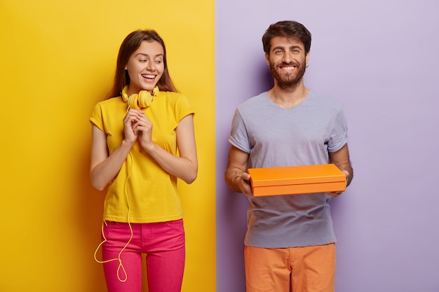Pleasant looking woman keeps hands in anticipation, looks curiously at cardboard box, being interesting what is inside. happy young man holds little contrainer or package, gives present to girlfriend
