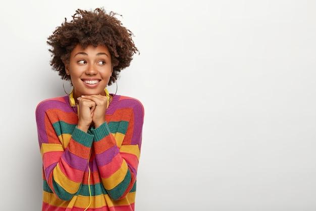 Una donna dall'aspetto piacevole tiene le mani sotto il mento, distoglie lo sguardo, vestita con un maglione a righe colorate