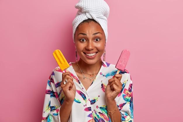 넓은 미소를 지닌 즐거운 외모의 여성은 화려한 아이스크림을 들고 머리에 가운과 수건을 입고 많은 칼로리를 얻고 맛있는 여름 디저트를 먹으라고 제안하며 장밋빛 벽에 포즈를 취합니다.