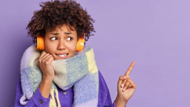 Una donna dall'aspetto piacevole e preoccupato con i capelli scuri e crespi guarda nervosamente e indica lo spazio della copia, ascolta la traccia audio in cuffia.