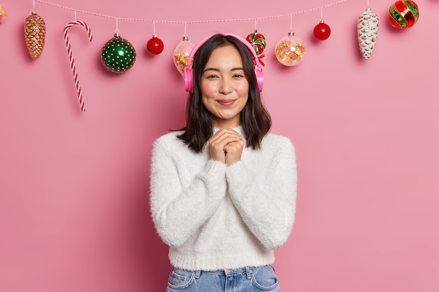 Приятно выглядящая молодая азиатская женщина держит руки вместе, имеет хорошее настроение, носит удобный белый свитер, слушает приятную мелодию в позах наушников.