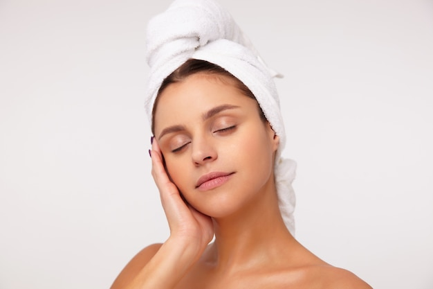 化粧をせずに、上げられた手で彼女の顔に優しく触れ、頭にタオルで白い背景の上に立っている間目を閉じたままで、快適に見える若い魅力的なブルネットの女性