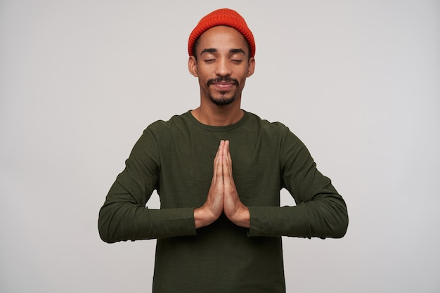 Pleasant looking young bearded dark skinned brunette guy raising hands in praying gesture while posing on white, keeping eyes closed and smiling slightly