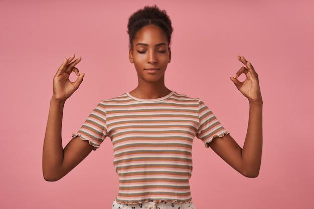 ピンクの壁に隔離された目を閉じて瞑想しながらムードラジェスチャーで手を上げる快適に見える若い茶色の髪の巻き毛の女性