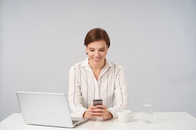Giovane donna graziosa dai capelli castani dall'aspetto piacevole con taglio di capelli corto alla moda che tiene lo smartphone nelle mani e sorride positivamente mentre chiacchiera con gli amici, isolato su bianco