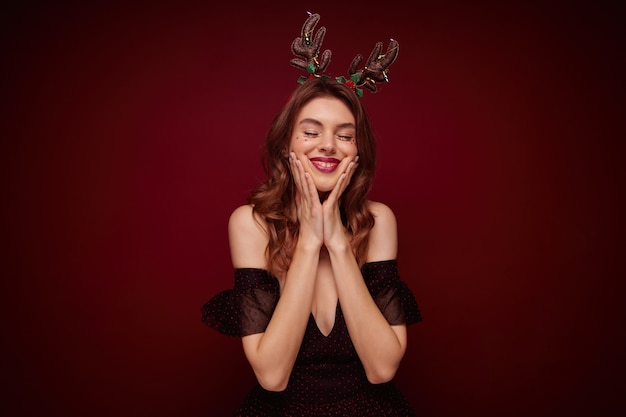 Pleasant looking young brunette lady with wavy hairstyle wearing festive clothes while posing, having funny holiday hoop on her head and smiling cheerfully