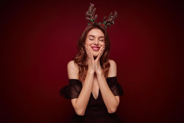 Приятно выглядящая молодая брюнетка с волнистой прической в праздничной одежде во время позирования, с забавным праздничным обручем на голове и весело улыбаясь