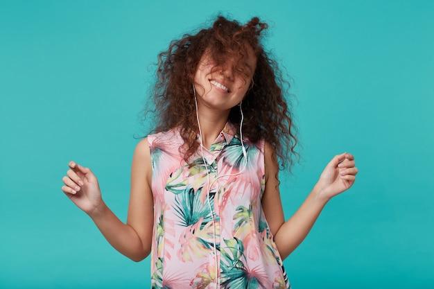 夏のブラウスで青に分離された、楽しく見える若い陽気な茶色の髪の巻き毛の女性は、幸せに髪を振って踊りながら手を上げます
