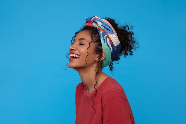 Pleasant looking young cheerful dark haired curly lady throwing back her head while laughing happily with closed eyes, standing over blue wall with hands down