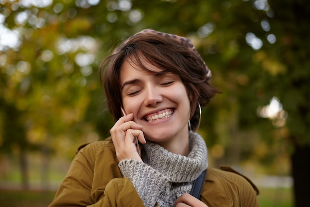 Bella femmina dai capelli corti allegra, dall'aspetto piacevole, tenendo gli occhi chiusi mentre sorride felicemente durante una bella conversazione telefonica, in piedi sopra il parco sfocato in abbigliamento caldo