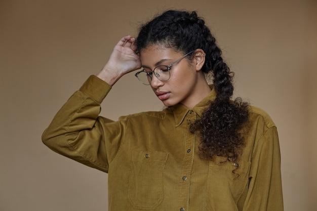 겨자 셔츠를 입고 그녀의 머리에 손을 들고 차분한 얼굴로 포즈를 취하는 안경에 즐거운 찾고 젊은 곱슬 갈색 머리 어두운 피부 아가씨