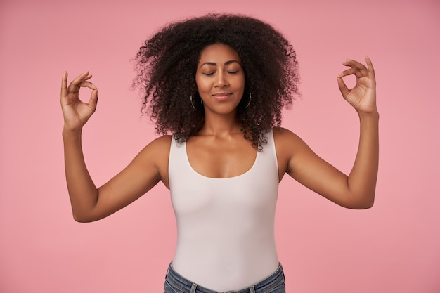 Приятно выглядящая молодая кудрявая женщина с темной кожей, держа глаза закрытыми во время медитации, позирует на розовом с нежной улыбкой и поднимая руки в знак мудры