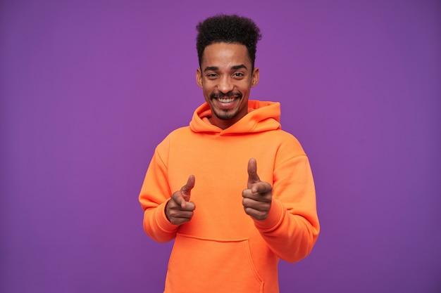 紫色のスポーティなカジュアルな服を着て、上げられた手で見せて、幸せそうに笑って、黒い肌の若い黒髪の茶色の目のひげを生やした男を見て楽しい