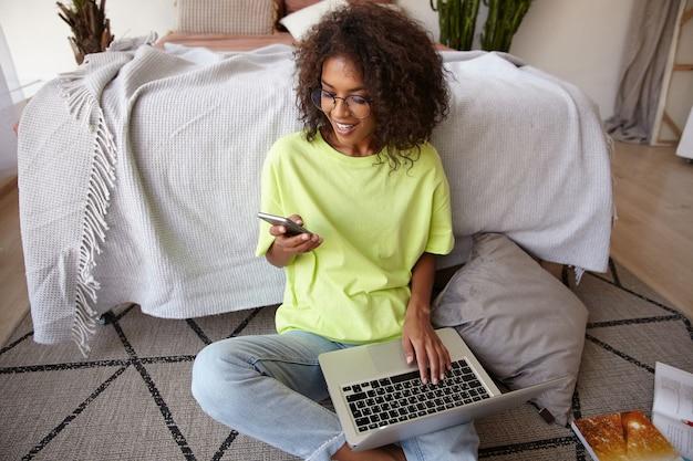 Приятно выглядящая молодая темноволосая женщина с кудрями работает на полу в спальне, держит смартфон в руке и держит ноутбук на ногах, получает хорошие новости, радостно улыбается